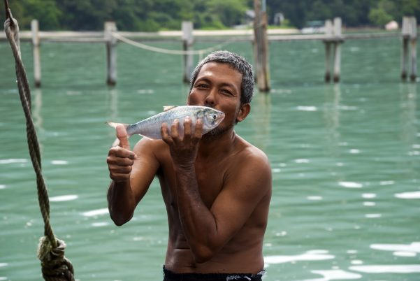 Fisherman with fish giving thumbs up
