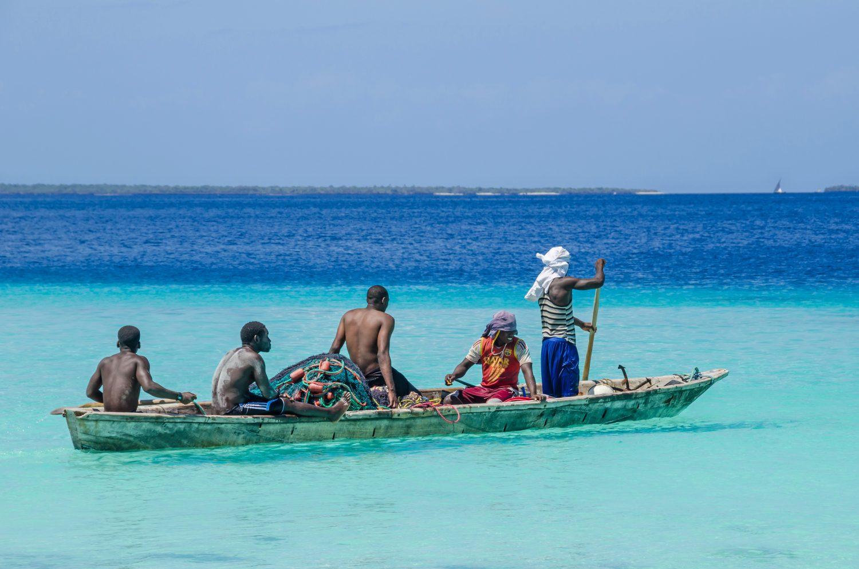 Five fishermen paddling a wooden boat